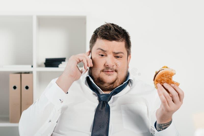uomo d'affari di peso eccessivo che parla sullo smartphone mentre mangiando hamburger immagini stock
