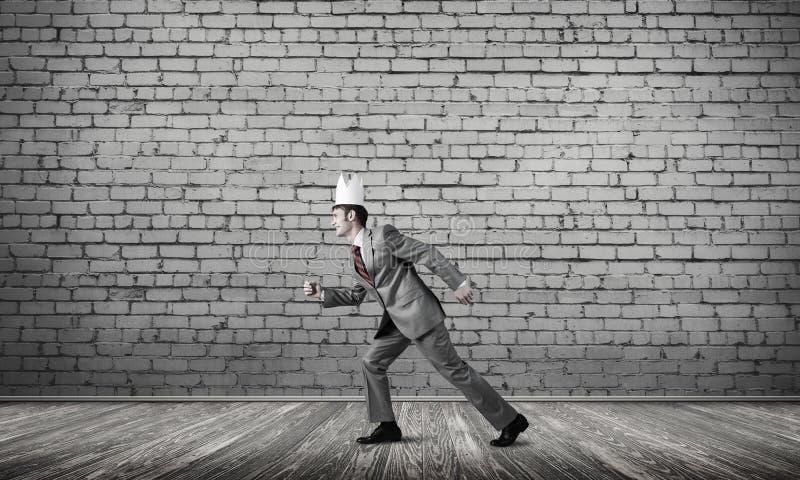 Uomo d'affari di re in vestito elegante che corre nella stanza vuota con il pavimento di legno fotografia stock libera da diritti