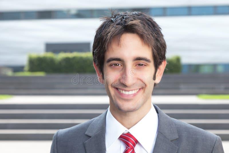 Uomo d'affari di risata con capelli neri fuori immagine stock
