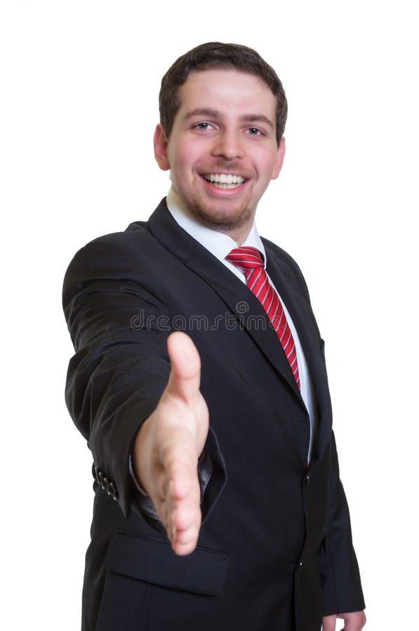 Uomo d'affari di risata in vestito nero che raggiunge mano per la stretta di mano fotografia stock