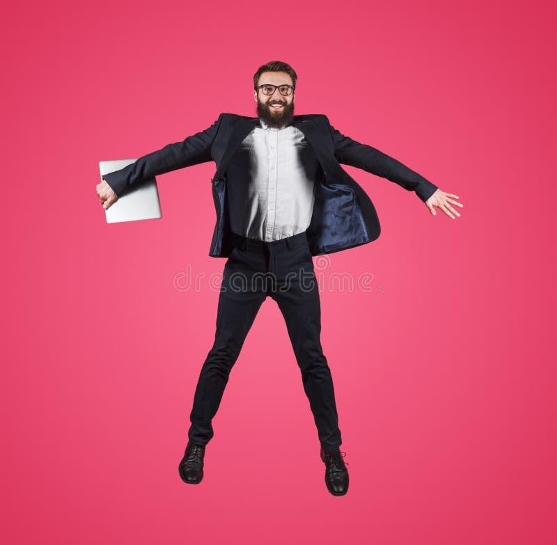 Uomo d'affari di salto con il computer portatile sul rosa fotografie stock