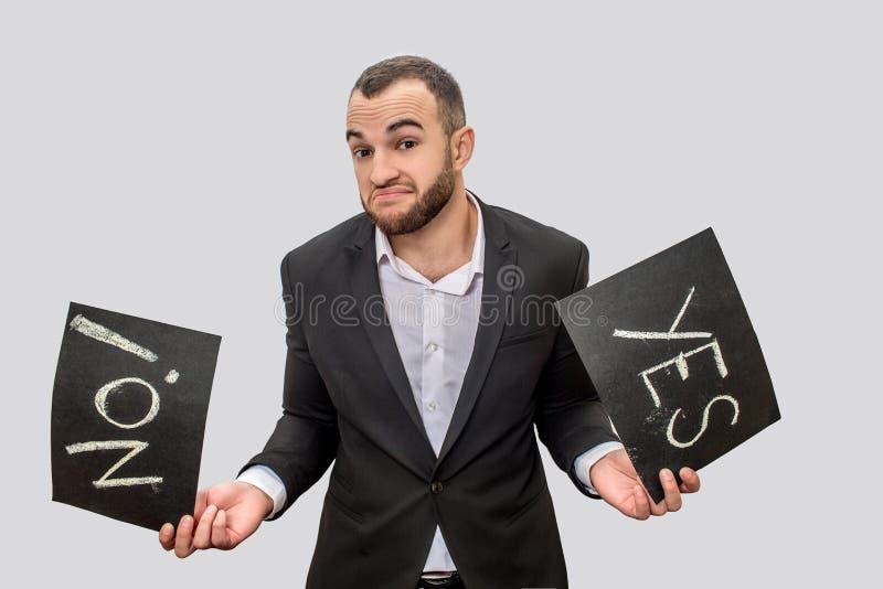 Uomo d'affari di Ypung in compresse nere della tenuta due del vestito con le parole scritte sì e no Considera la macchina fotogra fotografia stock libera da diritti