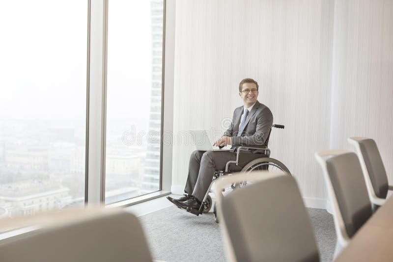 Uomo d'affari disabile sorridente con il computer portatile in sala del consiglio all'ufficio moderno fotografie stock