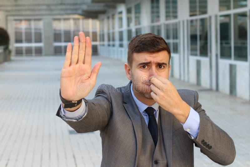 Uomo d'affari disgustato che odora qualche cosa di lordo immagine stock libera da diritti