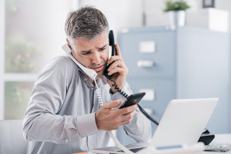 Uomo d'affari disperato sollecitato che lavora nel suo ufficio e che ha chiamate multiple, sta tenendo due microtelefoni e un tel fotografia stock