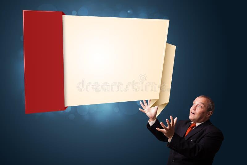 Uomo d'affari divertente che presenta lo spazio moderno della copia di origami fotografia stock libera da diritti