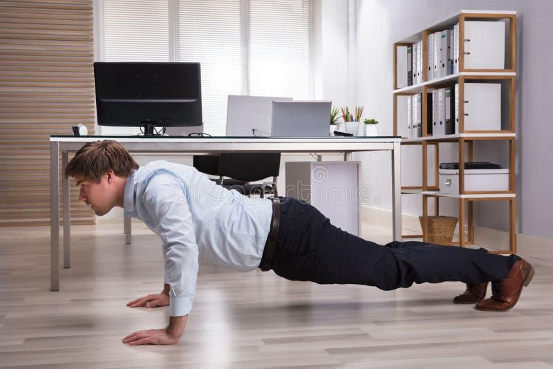 Uomo d'affari Doing Push Up in ufficio fotografia stock