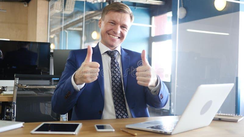 Uomo d'affari Doing Thumbs su da entrambe le mani alla macchina fotografica in ufficio fotografia stock libera da diritti