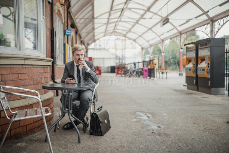 Uomo d'affari Drinking Coffee ed aspettare un treno immagini stock