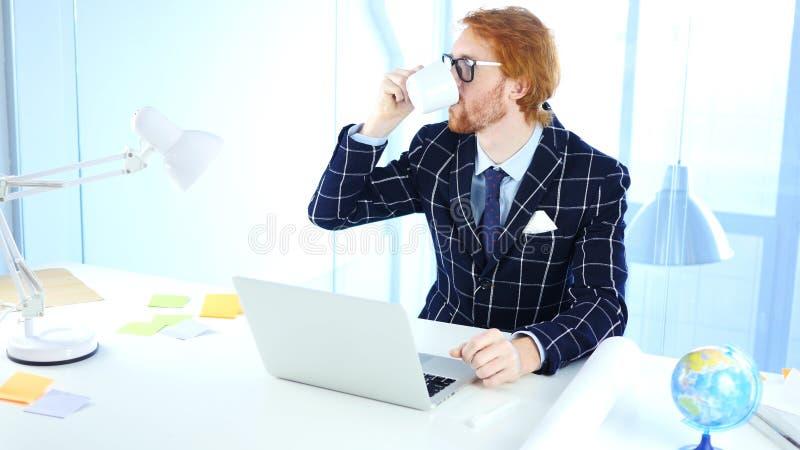 Uomo d'affari Drinking Coffee sul lavoro, progettista di rilassamento della testarossa delle free lance fotografia stock