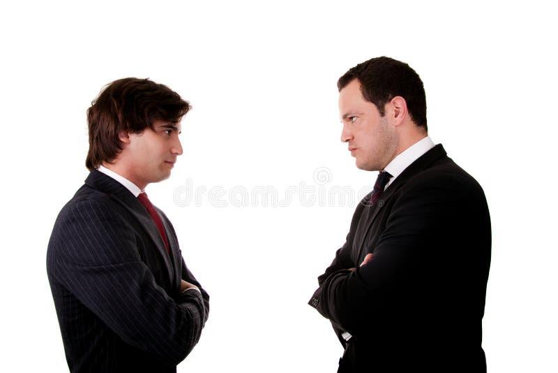 Uomo d'affari due che si leva in piedi faccia a faccia immagini stock libere da diritti