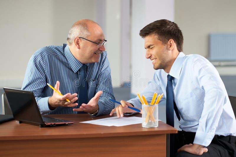 Uomo d'affari due con il computer portatile, ufficio come priorità bassa immagini stock