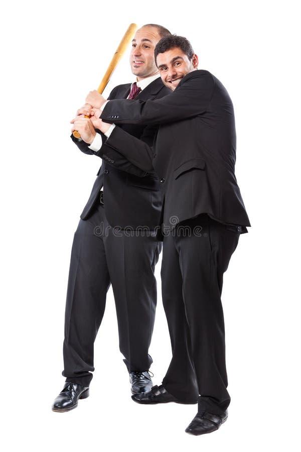 Uomo d'affari due e una mazza da baseball immagine stock