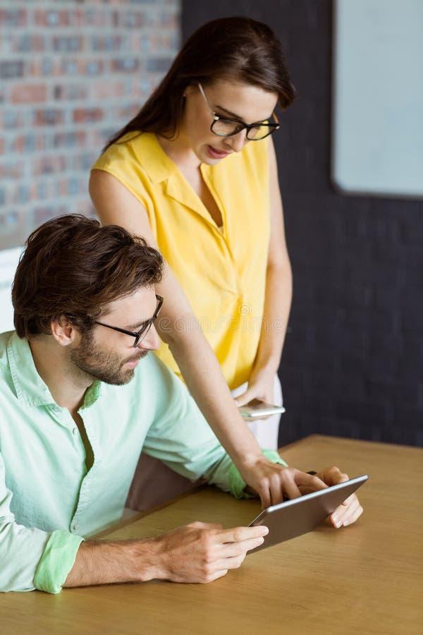Uomo d'affari e collega che interagiscono mentre per mezzo della compressa digitale immagini stock