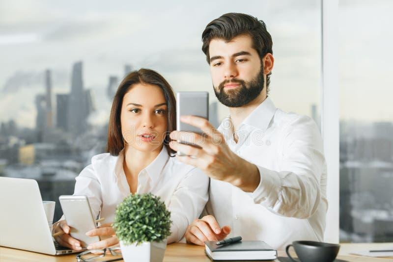 Uomo d'affari e donna attraenti che per mezzo dello smartphone fotografie stock