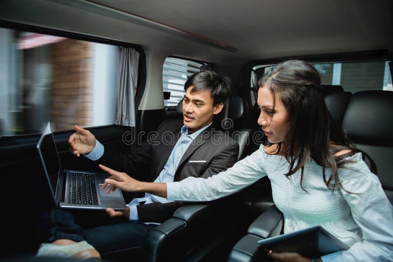 Uomo d'affari e donna che per mezzo del computer portatile sul sedile del passeggero dell'automobile fotografia stock