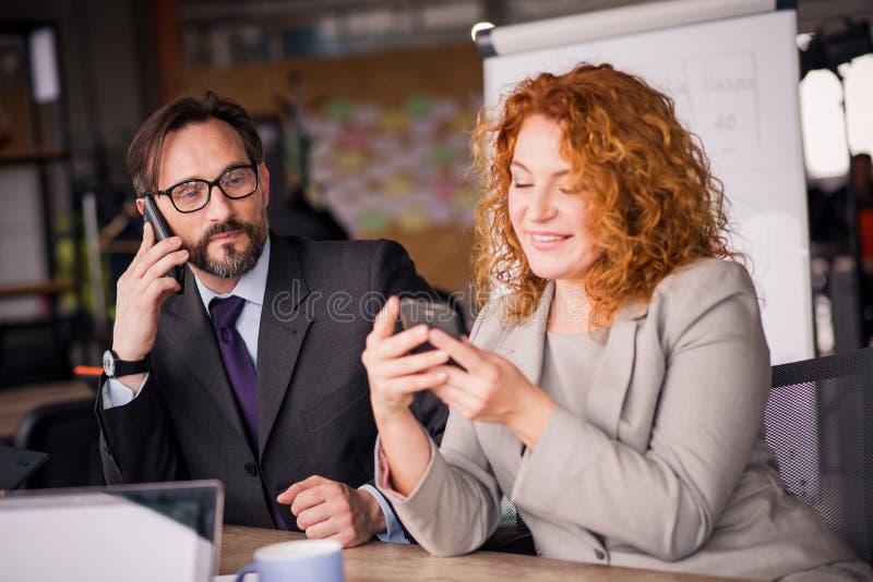 Uomo d'affari e donna di affari allo spazio di funzionamento che comunicano sul telefono immagini stock libere da diritti