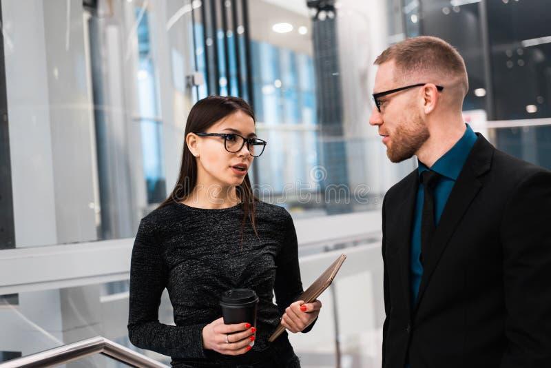 Uomo d'affari e donna di affari che discutono qualcosa durante la pausa caffè fotografia stock libera da diritti