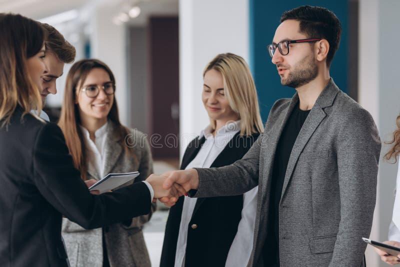 Uomo d'affari e donna di affari che stringono le mani nell'auditorium fotografie stock