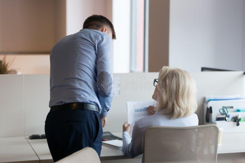 Uomo d'affari e donna di affari matura che lavorano insieme al rapporto finanziario fotografia stock