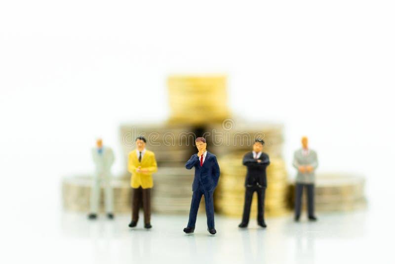 Uomo d'affari e pila miniatura di monete Uso di immagine per l'investimento, soldi di risparmio immagini stock
