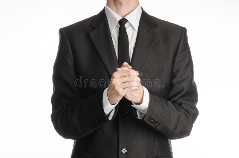 Uomo d'affari ed argomento di gesto: un uomo in un vestito nero con un legame ha piegato le sue mani davanti a lui ed a pregare,  fotografia stock