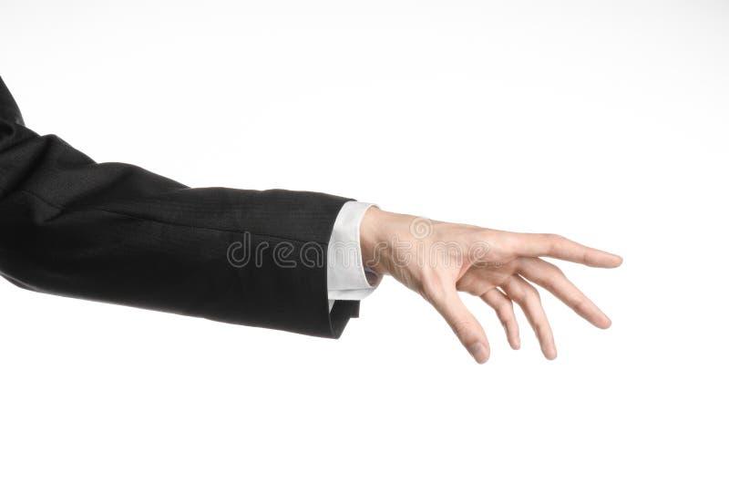 Uomo d'affari ed argomento di gesto: un uomo in un vestito nero ed in una camicia bianca che mostrano gesto di mano su un fondo b immagini stock libere da diritti