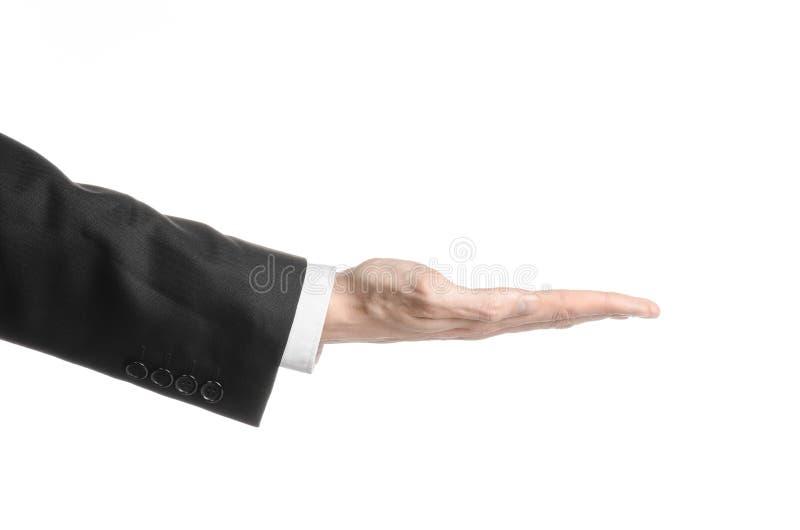 Uomo d'affari ed argomento di gesto: un uomo in un vestito nero ed in una camicia bianca che mostrano gesto di mano su un fondo b immagine stock libera da diritti