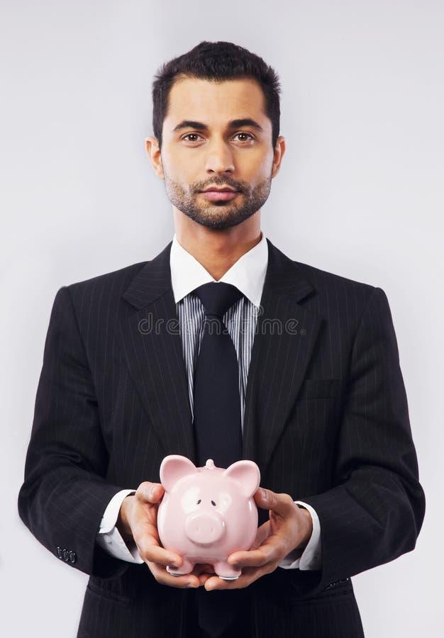 Uomo d'affari ed il suo porcellino salvadanaio fotografia stock libera da diritti