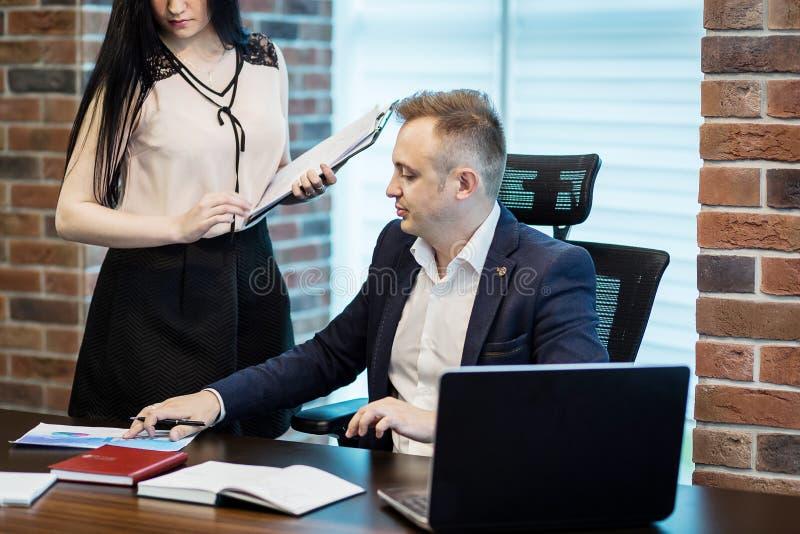 Uomo d'affari ed il suo segretario di aiuto nel suo ufficio Il Secre immagini stock