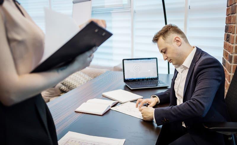 Uomo d'affari ed il suo segretario di aiuto nel suo ufficio Il Secre immagine stock