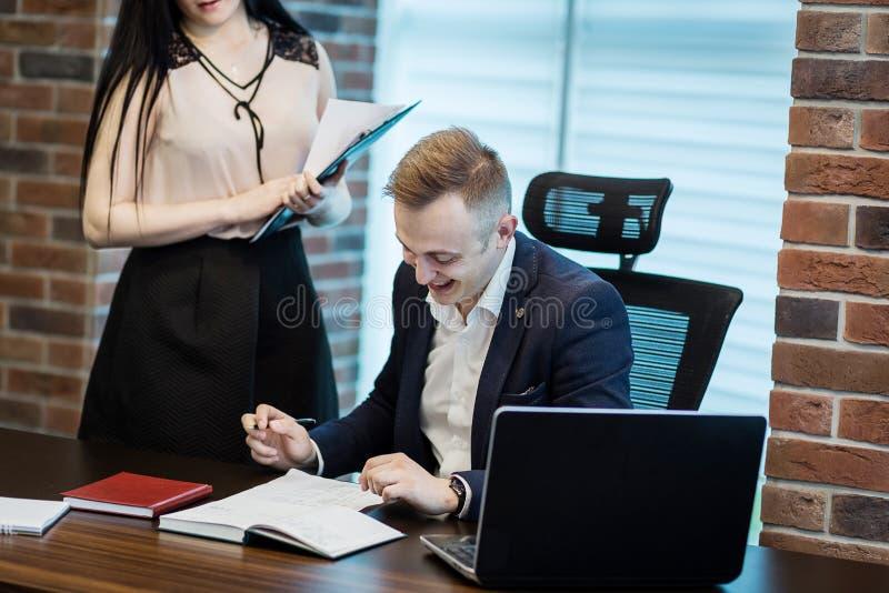 Uomo d'affari ed il suo segretario di aiuto nel suo ufficio Il Secre fotografia stock libera da diritti