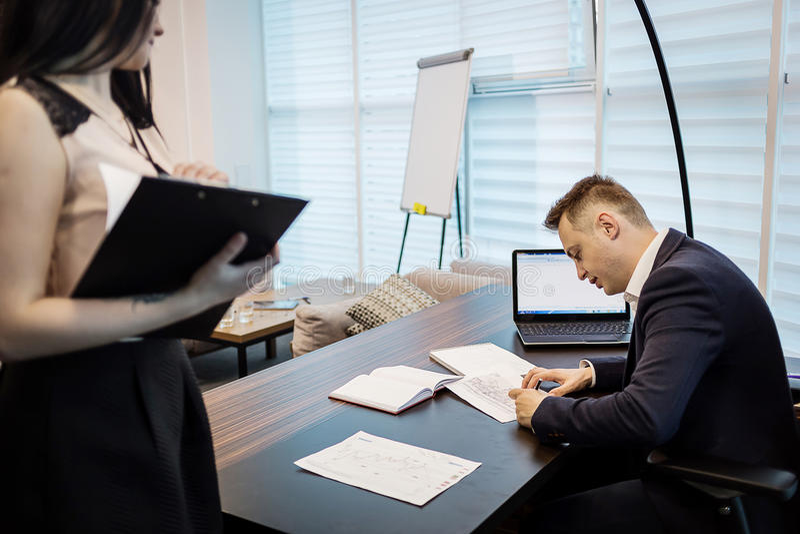 Uomo d'affari ed il suo segretario di aiuto nel suo ufficio Il Secre fotografie stock libere da diritti
