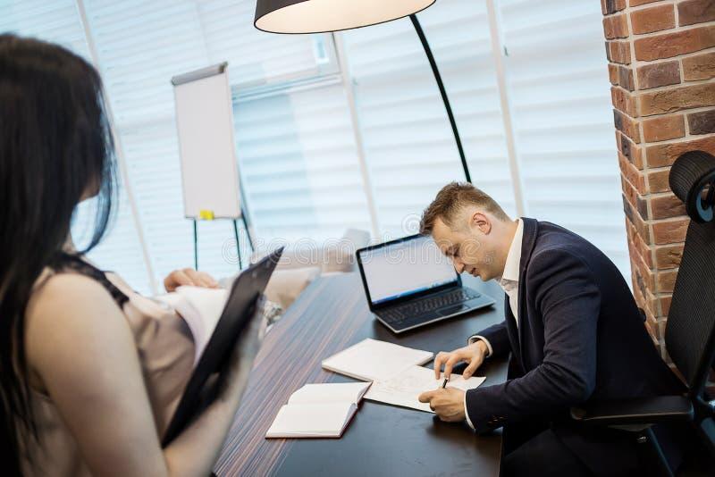 Uomo d'affari ed il suo segretario di aiuto nel suo ufficio Il Secre immagini stock libere da diritti