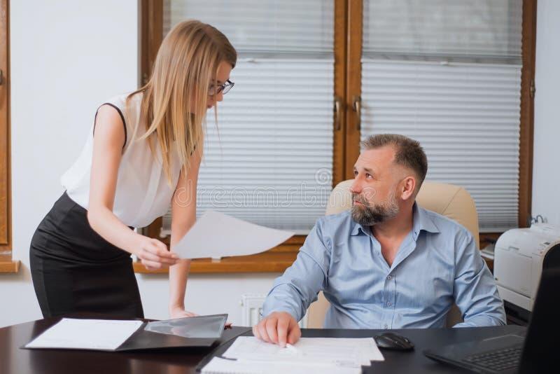 Uomo d'affari ed il suo segretario di aiuto nel suo ufficio immagine stock