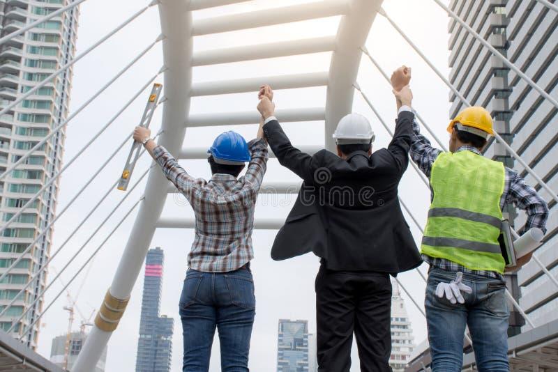 Uomo d'affari ed ingegneri che alzano armi che stanno dentro in città con il negoziato al successo fotografia stock libera da diritti