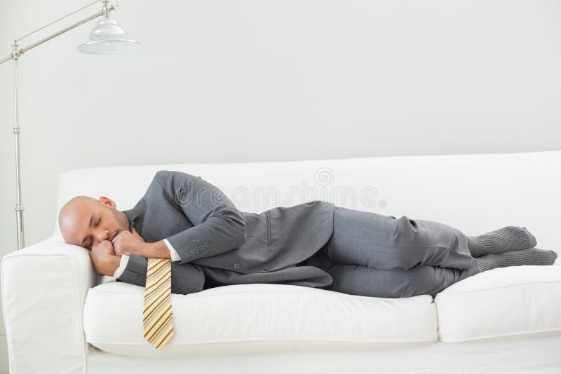 Uomo d'affari elegante che dorme sul sofà fotografia stock libera da diritti