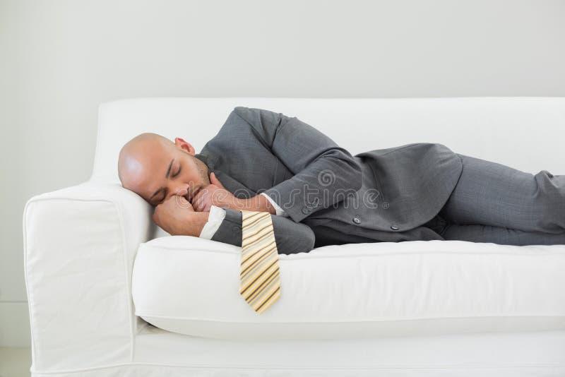 Uomo d'affari elegante che dorme sul sofà immagine stock
