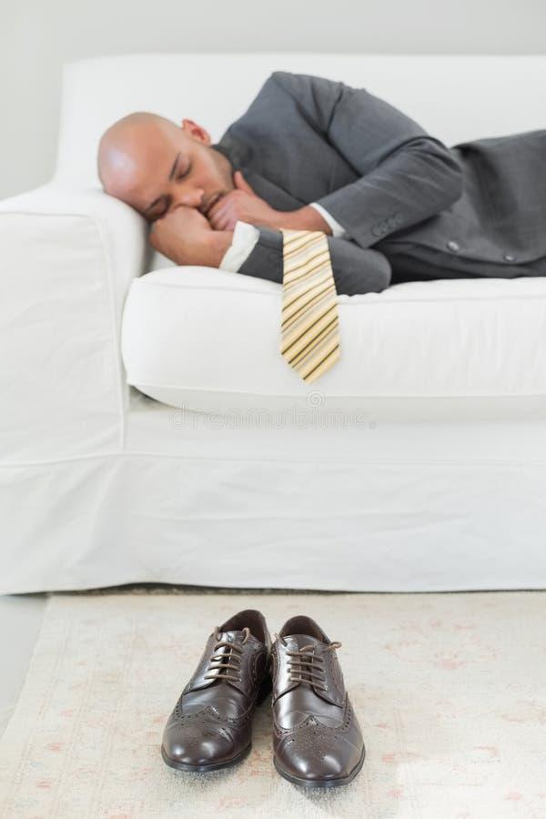 Uomo d'affari elegante che dorme sul sofà fotografia stock