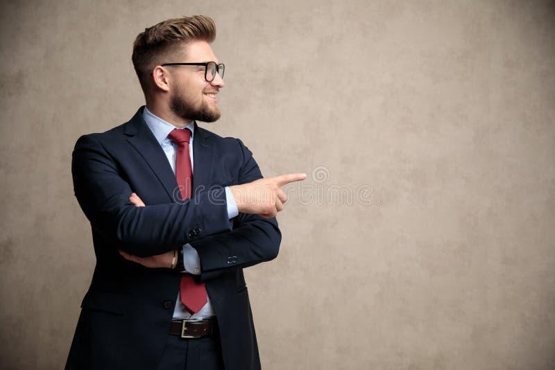 Uomo d'affari elegante che indica e che guarda lateralmente fotografie stock