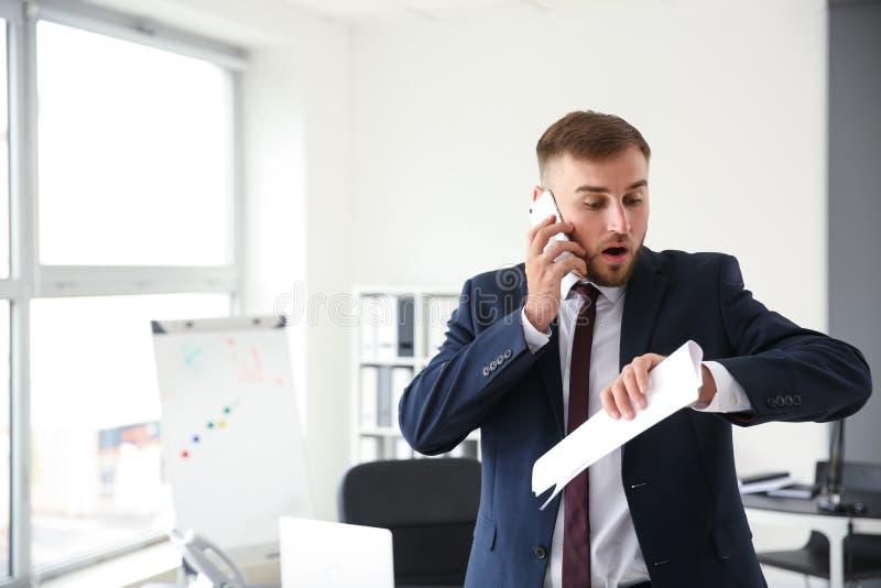 Uomo d'affari emozionale che esamina il suo orologio mentre parlando dal telefono in ufficio immagini stock