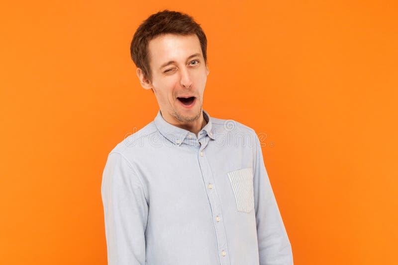 Uomo d'affari emozionale che porta camicia blu, strizzatina d'occhio alla macchina fotografica fotografia stock