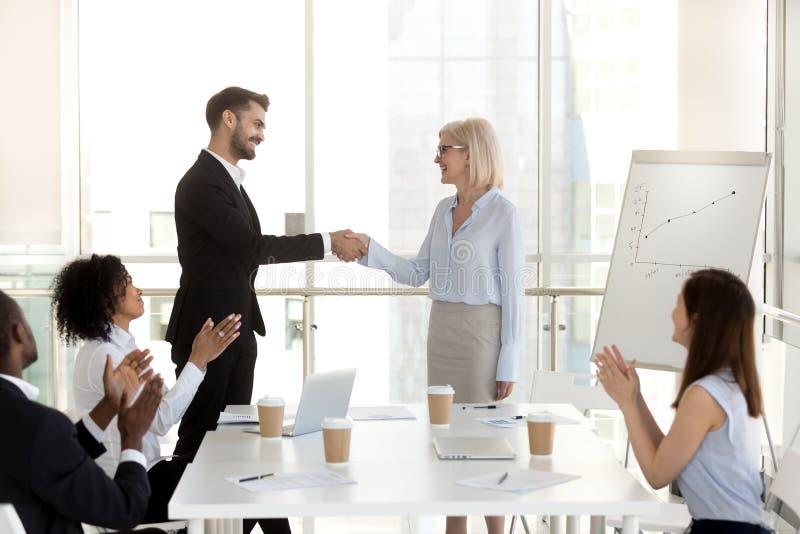 Uomo d'affari emozionante che stringe mano della donna di affari alla riunione di società fotografie stock libere da diritti