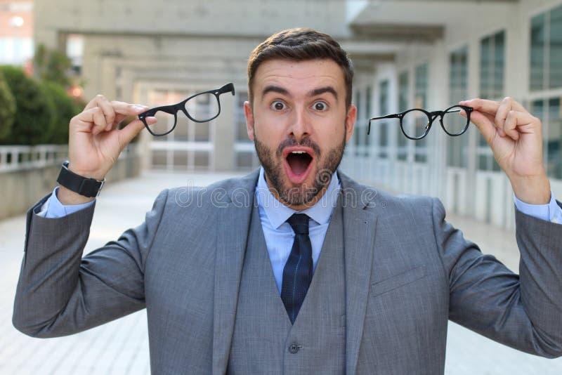 Uomo d'affari emozionante che tiene due paia degli occhiali fotografia stock libera da diritti