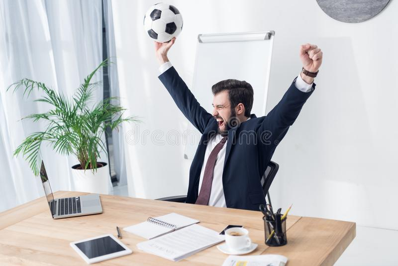 uomo d'affari emozionante in vestito con pallone da calcio nel luogo di lavoro fotografia stock libera da diritti