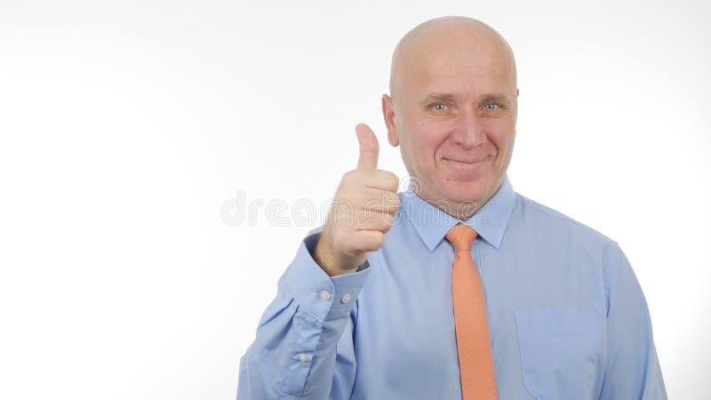 Uomo d'affari entusiasta Smile e fare i pollici gesti sui buoni di un lavoro fotografia stock libera da diritti