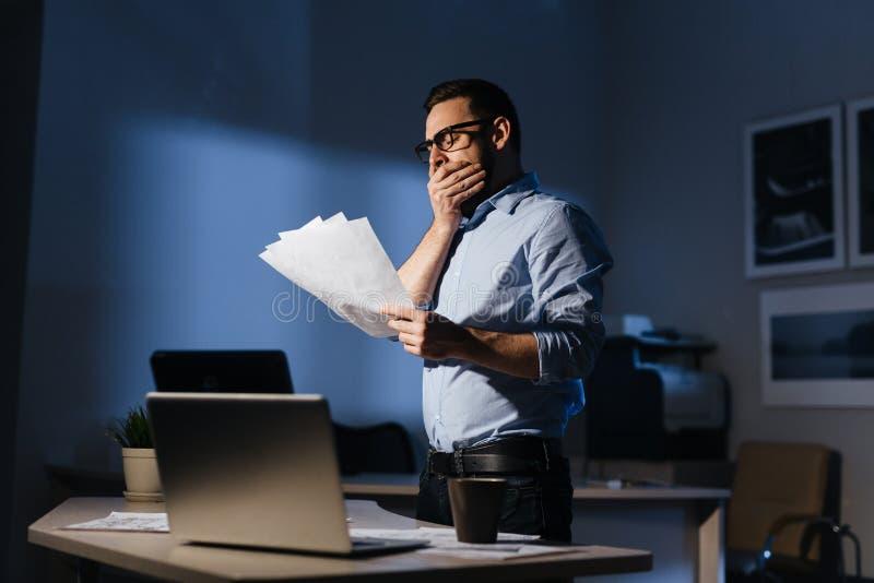Uomo d'affari esaurito Working in ufficio alla notte immagini stock