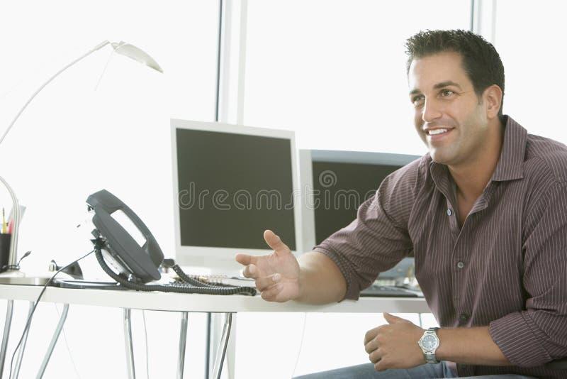 Uomo d'affari Explaining While Sitting dalla scrivania immagini stock
