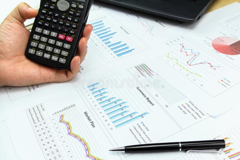 Uomo d'affari facendo uso del calcolatore con il grafico commerciale immagini stock