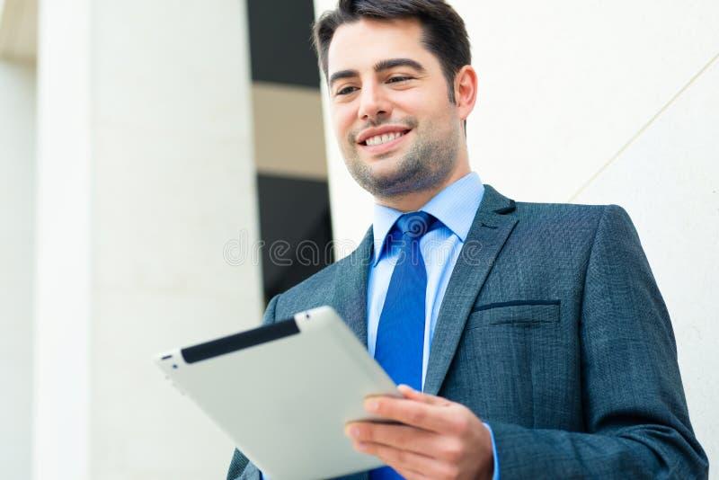 Uomo d'affari facendo uso del computer della compressa fotografie stock libere da diritti